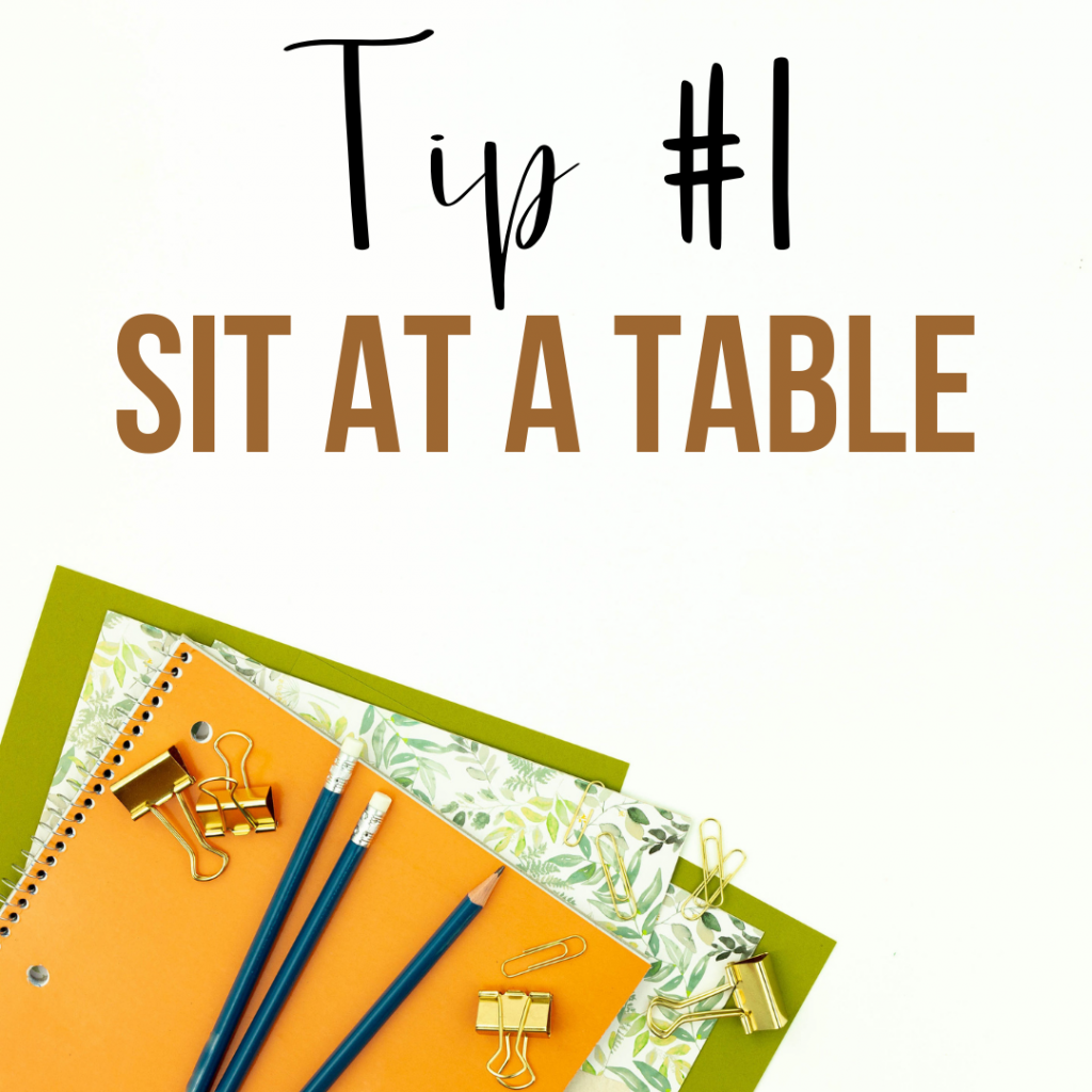 sit at a table during the conference